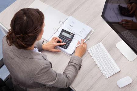 請求書を計算する若い女性会計士の高角度のビュー