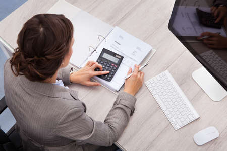 accountants: High Angle View Of Young Female Accountant Calculating Bills Stock Photo