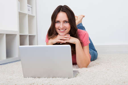 Portrait Of Smiling Young Woman Lying On Floor In Front Of Laptop photo