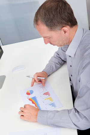 High Angle View Of Businessman Analyzing Graph In Office photo