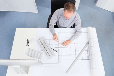 architect drawing: Portrait Of A Mature Architect Drawing Plan On Blueprint In Office