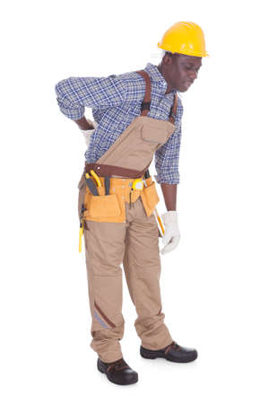 back ache: Young Repairman Having Back Ache Over White Background