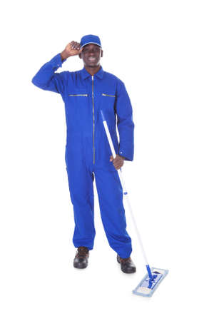 boiler suit: Young Man In Blue Boiler Suit Holding Mop Over White Background