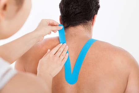 convulsion: Mujer joven que aplica Physio Especial Cinta de espalda del hombre