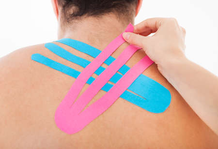 Young Woman Applying Special Physio Tape On Mans Back photo