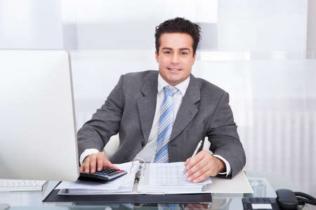 Portrait Of Happy Young Businessman Sitting At Desk Calculating Finance photo