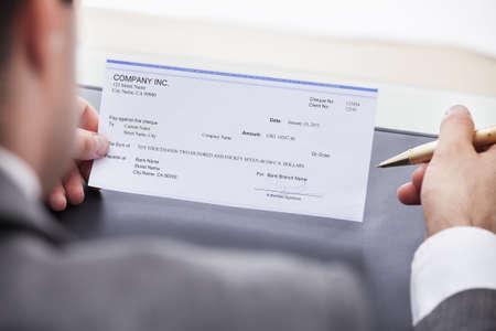 空白の小切手を充填ビジネスマンのクローズ アップ