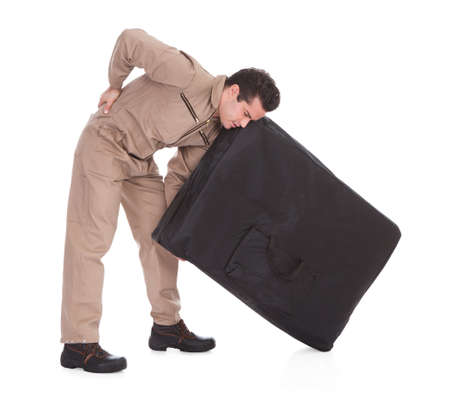 Young Man Suffering From Back Pain Lifting Luggage Over White Background photo