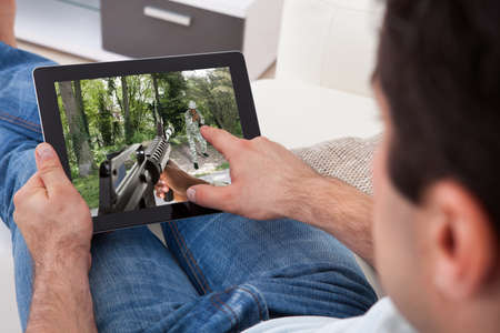 gun room: Close-up Of Young Man Playing Game On Digital Tablet At Home