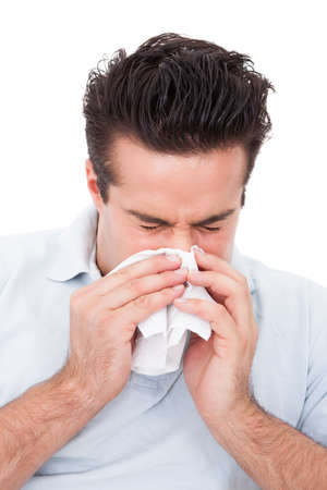 Young Man Blowing His Nose In A Tissue Over White Background photo