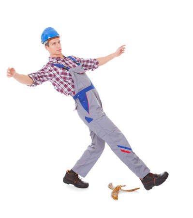 Portrait Of Young Male Worker Falling On White Background photo