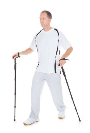 walking pole: Portrait Of Man Walking With Hiking Pole Over White Background