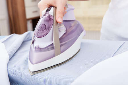 steam iron: Close-up Of Womans Hand Ironing Clothes On Ironing Board Stock Photo