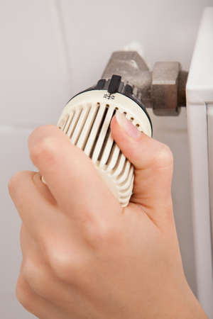 Close-up Of Persons Hand Adjusting Temperature By Thermostat photo