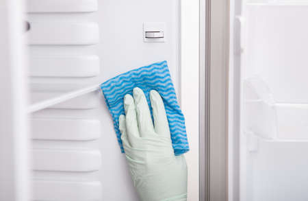 handglove: Close-up Of A Young Woman Cleaning Refrigerator