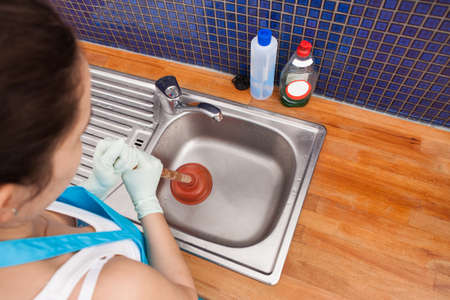 handglove: High Angle View Of A Woman Using Plunger In Kitchen Sink