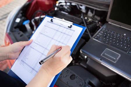 mecanico automotriz: Redacci�n mec�nico de hombre a Portapapeles Mientras Examinar motor de coche Foto de archivo