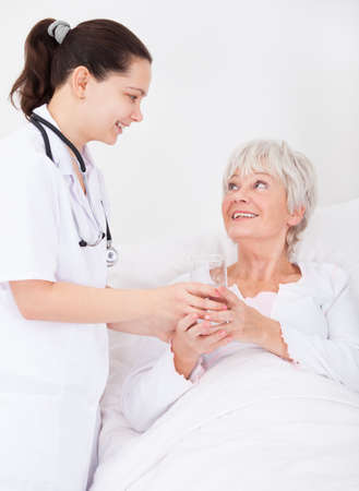 Young Female Doctor Giving Glass Of Water To Senior Female Patient photo