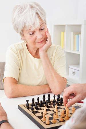 echtgenoot: Senior Vrouw speelt schaak met haar man
