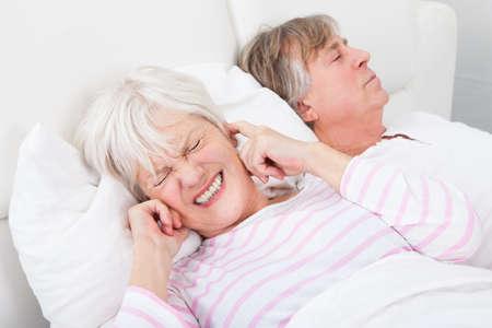 snoring: Portrait Of Senior Angry Woman Awaken By Her Husband Snoring