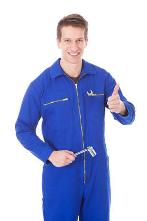 studio happy overall: Portrait Of Young Male Mechanic Holding Equipment Over White Background