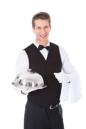 cloche: Young Male Waiter Holding Cloche Lid Cover Over White Background Stock Photo
