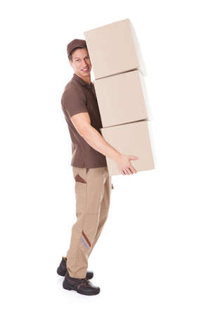 delivery service: Handsome Delivery Man Carrying Stack Of Cardboard Boxes Over White Background Stock Photo