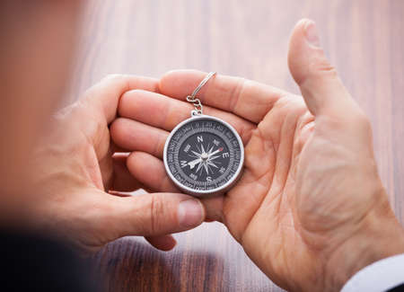 orienteering: Close-up Of Hand Holding Compass On White Background Stock Photo