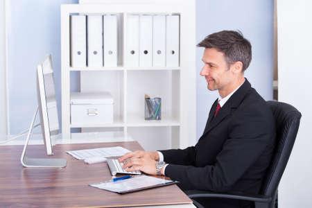 mature businessman: Portrait Of Mature Businessman Using Computer At Desk Stock Photo