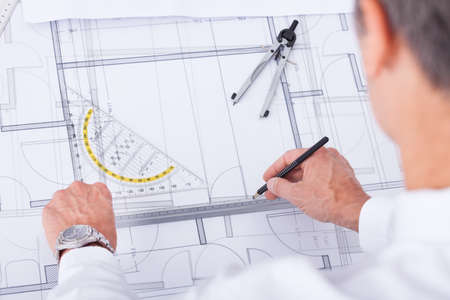 architect office: Close-up Of Male Architect Drawing Blueprint In Office