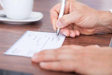 Mannelijke Hand invullen van het bedrag op een cheque Stockfoto