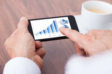 Close-up Of A Businessman Analyzing Graph On Smartphone photo