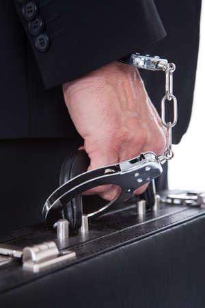 suit case: Close-up Of Person Wearing Handcuff Attached To Suitcase