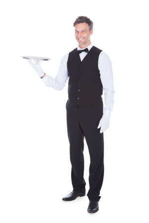 Portrait Of Happy Male Waiter Holding Empty Tray photo