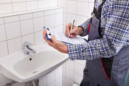 Close-up Of Plumber Standing In Front Of Washbasin Writing On Clipboard photo
