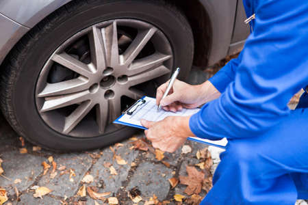 car workshop: Close-up Of Worker Writing On Clipboard Sitting Near Car Stock Photo