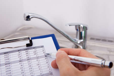 watertap: Hand Writing With Pen Water Consumption Level In Front Of Watertap