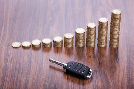 Stack Of Coins With Black Car Key Placed On Desk photo