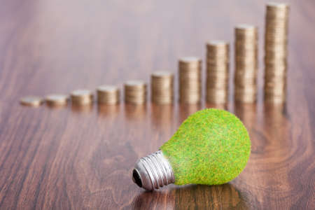 sustentabilidad: Close-up de la bombilla ecológica delante de las monedas apiladas en mesa de madera