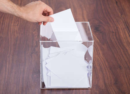 Close-up Of Person Hands Putting Ballot In Box Kept On Wooden Table photo
