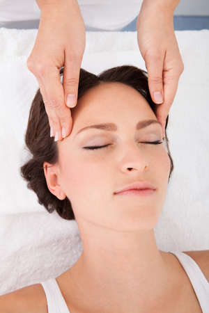 Young Woman With Eyes Closed Getting Massage Treatment From Masseuse Stock Photo - 25349708
