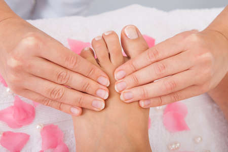 pressure massage: Close-up Of Womans Feet Receiving Foot Massage In Spa Stock Photo