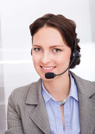 Portrait Of Happy Young Female Telephone Operator With Headphones photo