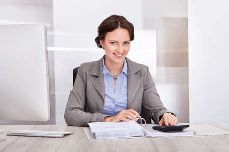 account executives: Portrait Of Smiling Young Female Accountant Calculating Bills Stock Photo