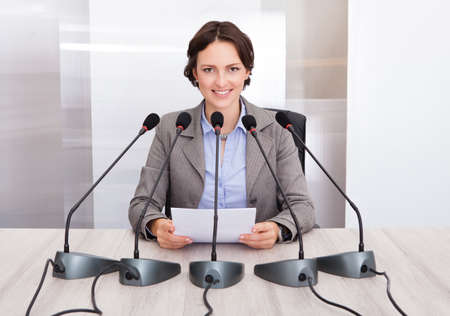 Smiling Businesswoman Holding Paper Speaking In Front Of Multiple Microphones photo