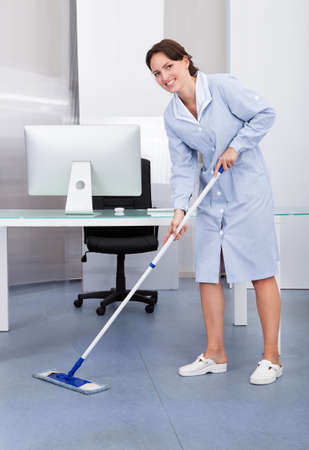 office cleanup: Portrait Of Happy Female Janitor Cleaning Floor At Office