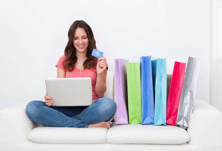 Junge Frau, die online Sitzen Neben Reihe von Einkaufstaschen