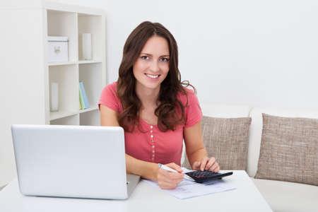 Retrato de una mujer joven sonriente Cálculo Finanzas Bills