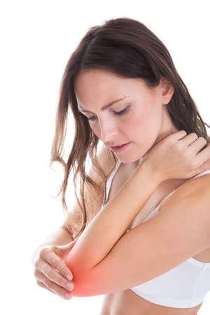 codo: Mujer joven con dolor en su codo Sobre Fondo Blanco Foto de archivo