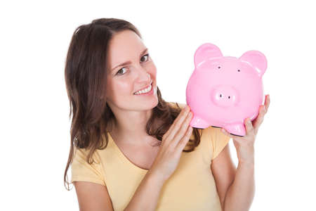 Close-up Of A Smiling Woman Holding Piggybank Over White Background photo
